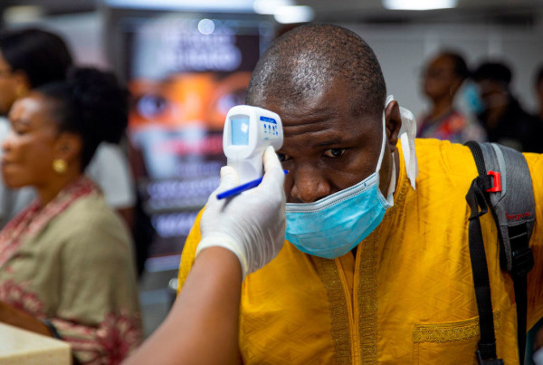 A passenger's body temperature is being tested at the gate of entry upon arrival at the Murtala International Airport in Lagos, on March 2, 2020. - Nigeria is monitoring 58 people who had contact with an Italian man infected with the new coronavirus, the health minister said Monday, as officials scrambled to stop the disease spreading.Africa's most populous country on Friday confirmed the first case of the virus in sub-Saharan Africa after the patient was diagnosed in the economic hub Lagos. (Photo by BENSON IBEABUCHI / AFP) (Photo by BENSON IBEABUCHI/AFP via Getty Images)